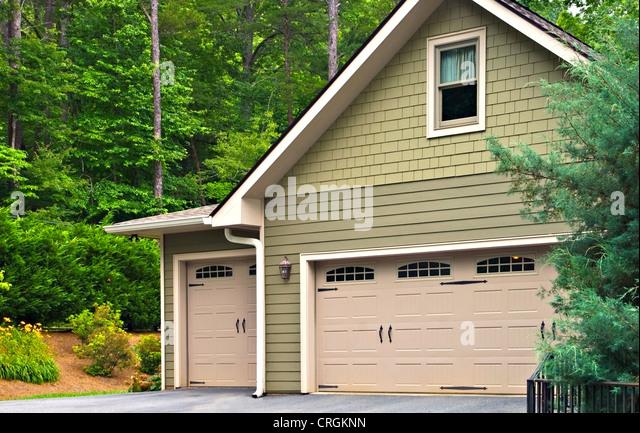 Garagentore auf ein modernes Haus. Doppeltür mit Fenster auf einer Seite und eine Aufrechnung Single daneben. Stockbild