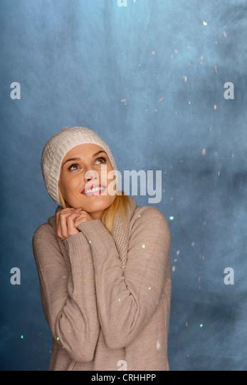 Frau trägt stricken Hut vor verschneiten Hintergrund, Porträt Stockbild