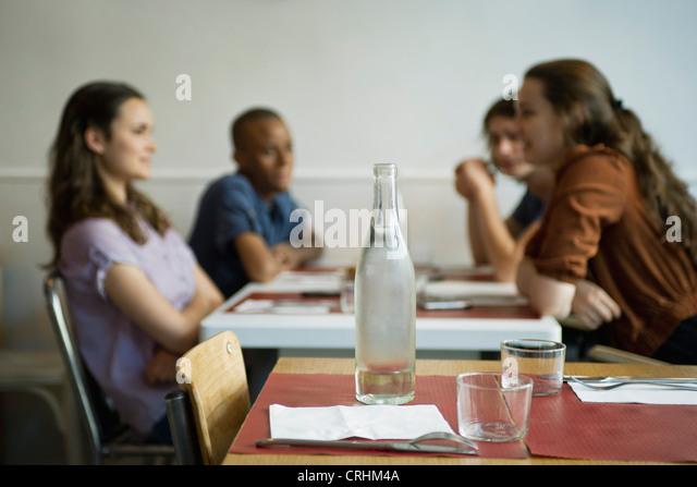 Freunde hängen in Café, konzentrieren sich auf leere Tabelle im Vordergrund Stockbild