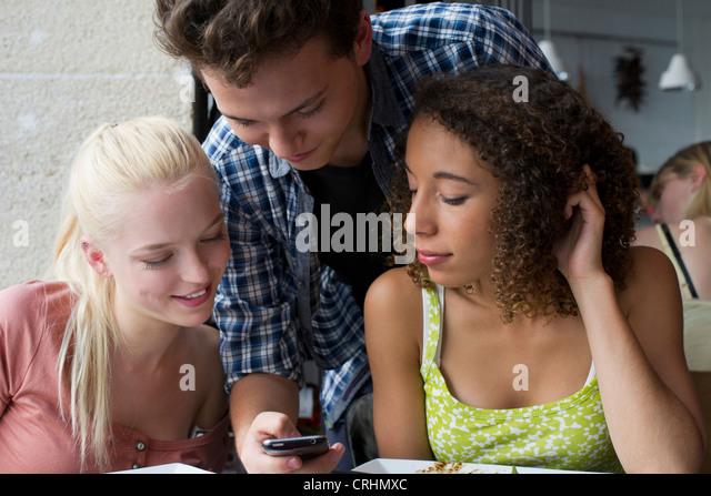 Freunde, die miteinander im Handy suchen Stockbild