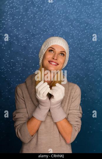 Frau trägt zu stricken, Mütze und Handschuhe vor verschneiten Hintergrund, Porträt Stockbild
