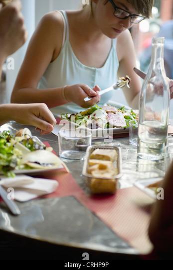 Junge Frau, die Mahlzeit im café Stockbild