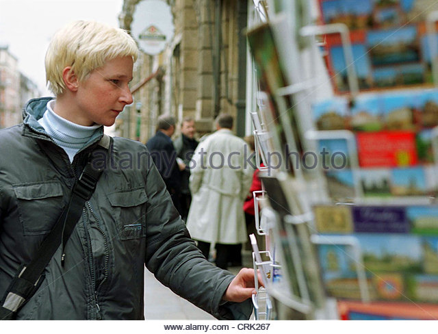 Eine junge Frau wählt aus Postkarten Stockbild