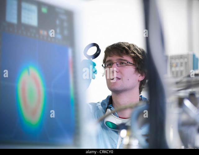 Wissenschaftler untersuchen Objektiv im Labor Stockbild