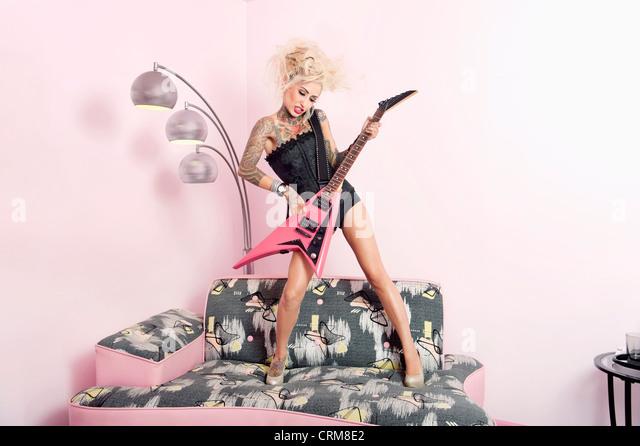 Junge Frau im Korsett Gitarre im stehen auf Möbeln Stockbild