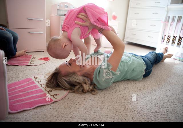 Mutter hält ihr elf Monate altes Mädchen und spielen im Schlafzimmer. Stockbild