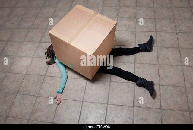 Teenager-Mädchen unter Karton liegen Stockbild