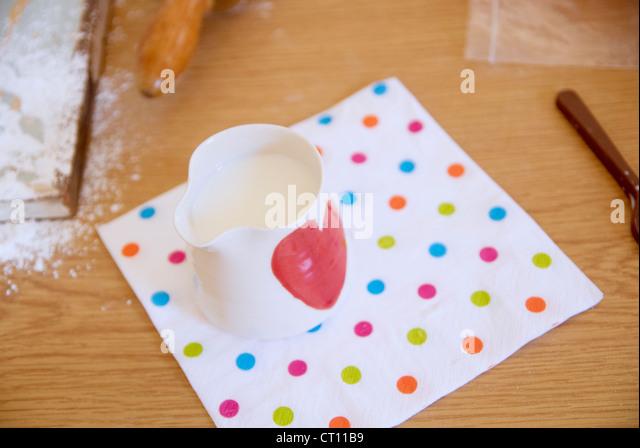 Krug mit Milch auf Handtuch in Küche Stockbild