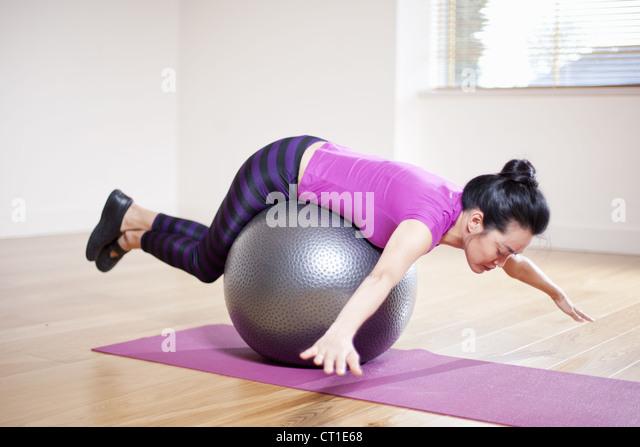 Frau balancieren auf Ball im Yoga-studio Stockbild