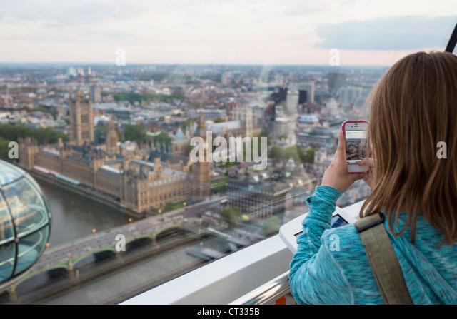 Ein junges Mädchen nimmt ein Foto vom London Eye Stockbild