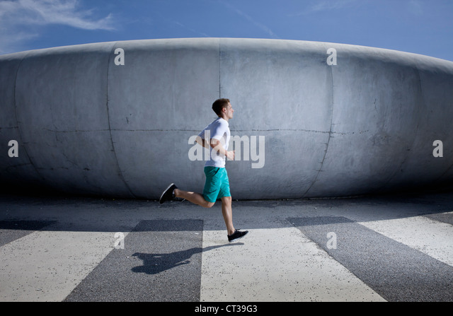 Mann läuft im Industriegebiet Stockbild