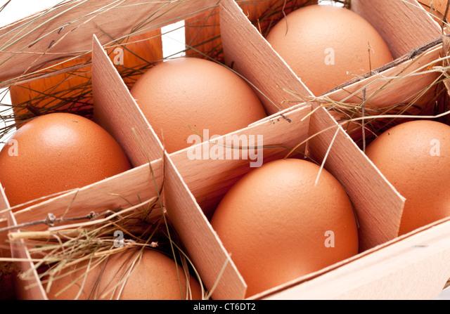 Eiern mit einem Strohhalm in einem hölzernen Korb Stockbild