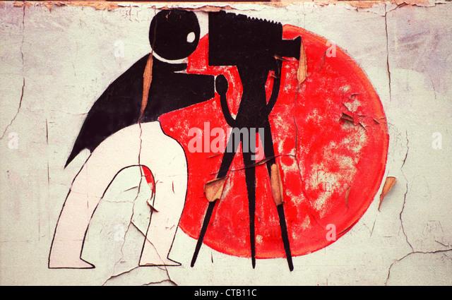 Eine Art-déco-Illustration eines Fotografen mit Kamera und Stativ schmückt die Wand eines verlassenen Stockbild
