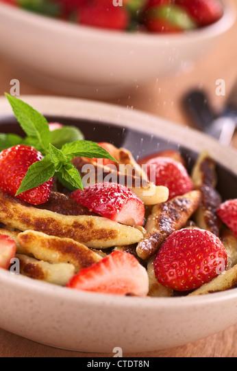 Schupfnudeln (schwäbische Kartoffel Nudeln aus Süddeutschland) mit frischen Erdbeeren, Zucker und Zimt Stockbild