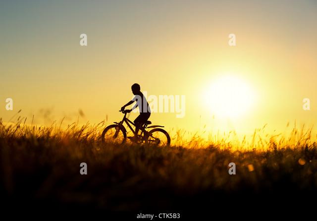 Junge mit dem Fahrrad durch Rasen bei Sonnenuntergang. Silhouette. UK Stockbild