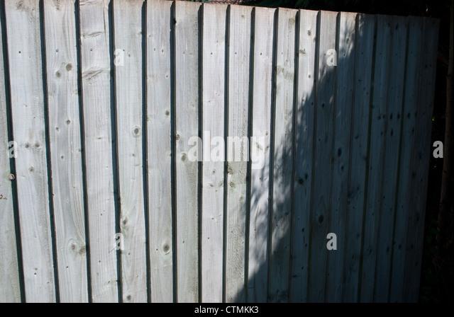 Grauen Holzzaun Panel mit aufrecht Lamellen halb im Schatten Stockbild