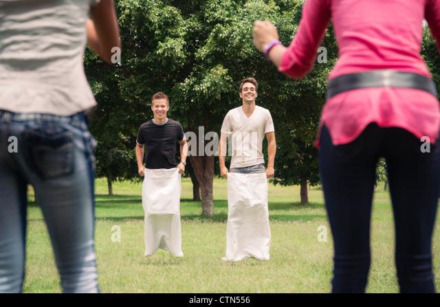 Freunde, die Spaß, junge Männer spielen Sackhüpfen im Stadtpark mit Frauen Händeklatschen und Stockbild