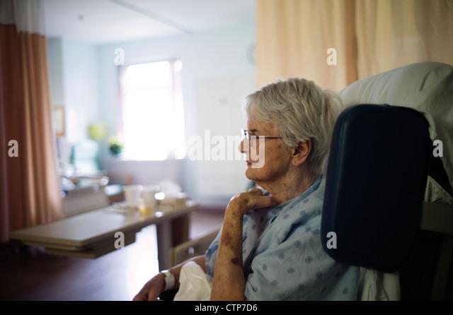 Alte Frau sitzt im Rollstuhl im Krankenhaus. Stockbild