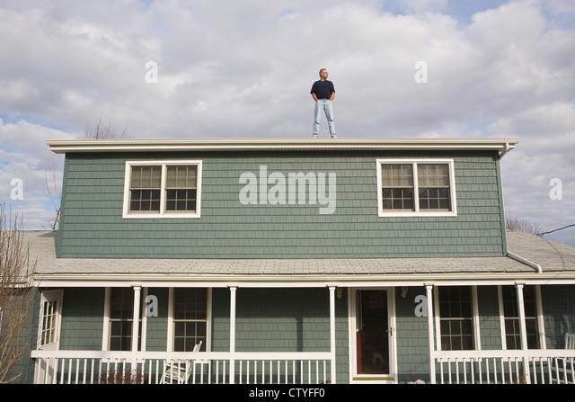 Mann auf Hausdach Stockbild