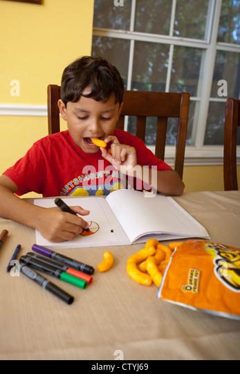 7 und 8 Jahre alten mexikanisch-amerikanischen jungen Snacks auf Junk-Food, Cheetos, während des Zeichnens Stockbild