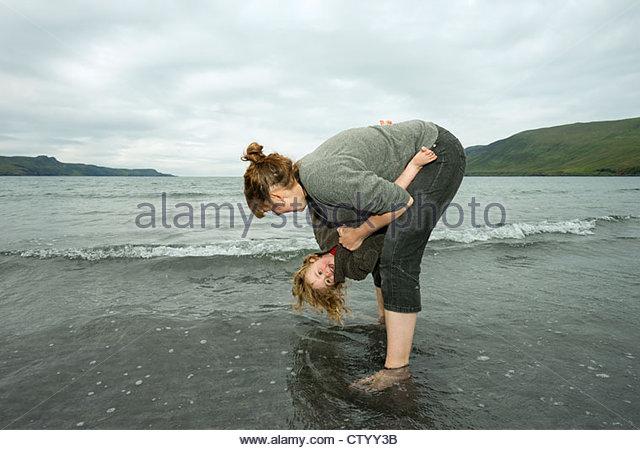 Mutter und Tochter spielen in Wellen Stockbild