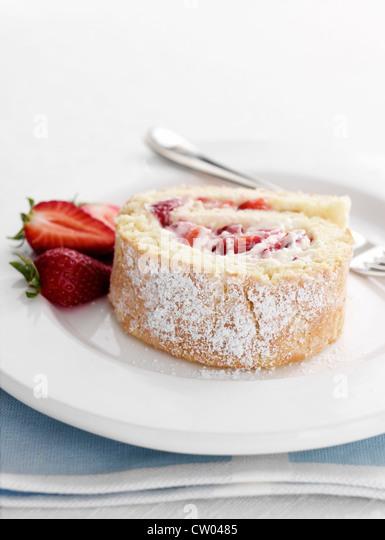 Teller mit Erdbeer-Biskuitrolle Stockbild