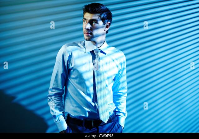 Porträt von eleganten Geschäftsmann sucht beiseite mit blinden Schattierungen auf Hintergrund Stockbild