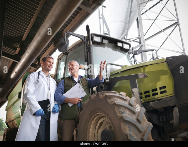 Landwirt und Tierarzt mit einem Traktor Stockbild