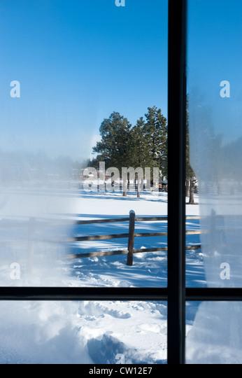 Ein Blick aus dem Kabinenfenster mit Kondensation mit Blick auf eine verschneite Berglandschaft Stockbild