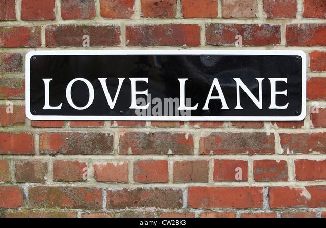 Straßenschild für Love Lane auf Ziegelmauer Stockbild