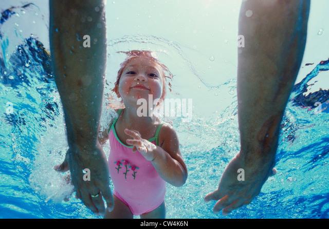 Nahaufnahme des Vaters Hände Annäherung an seine Tochter unter Wasser Stockbild