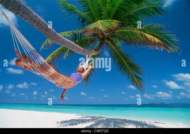 Frau in Hängematte unter Palmen inmitten der idyllischen Urlaub Stockbild