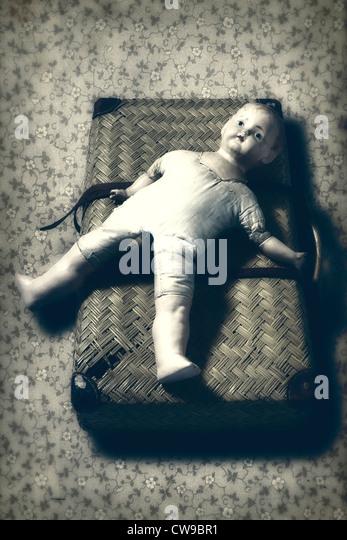 eine alte, kaputte Puppe liegt auf einem alten Koffer Stockbild