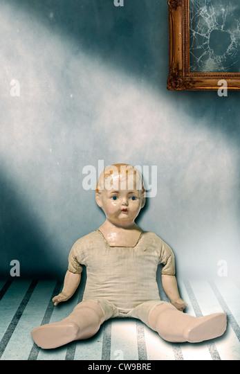 eine alte Puppe sitzt in einem schäbigen Zimmer Stockbild