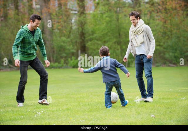 Jungen Fußball spielen mit zwei Männern in einem park Stockbild