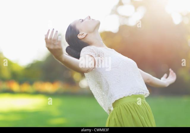 Junge Frau fällt auf Wiese Stockbild