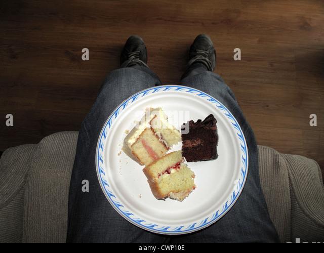 Teller mit Kuchen schneidet auf des Mannes Schoß direkt über Stockbild