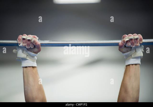 Turnerin der Arme greifen Reck, beschnitten Stockbild