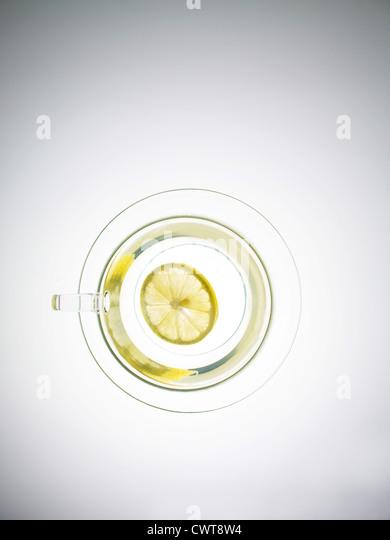 Scheibe der Zitrone in eine transparente Teetasse von oben Stockbild