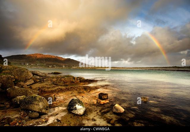 Regenbogen erstreckt sich über noch ländliche See Stockbild