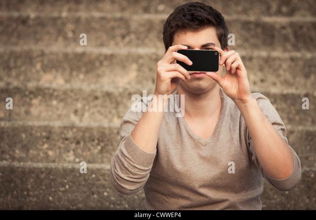Mann unter Bild mit Handy Stockbild