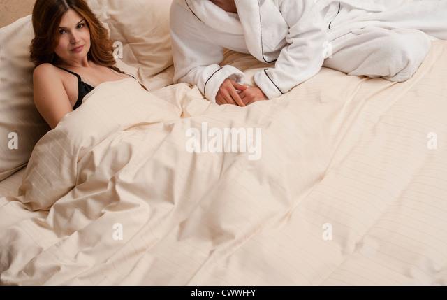 Paar mit auf Bett zusammen Stockbild