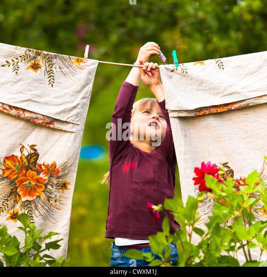 Süßes fünfjähriges Mädchen mit Wäscheklammer und die Wäscheleine Stockbild