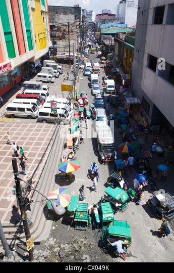 ein Blick auf eine Straße mit vielen Autos und Geschäften, Philippinen. Stockbild