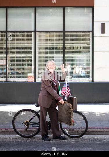 Ältere Mann mit Fahrrad machen Peace-Zeichen Stockbild