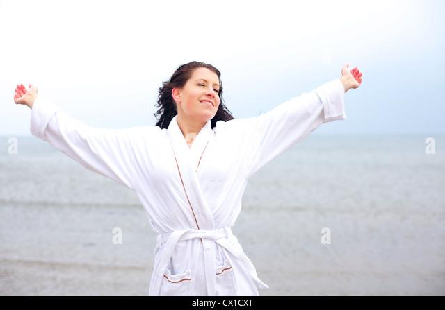 Frau im Bademantel genießen die kühle frische Morgenluft des Strandes Stockbild
