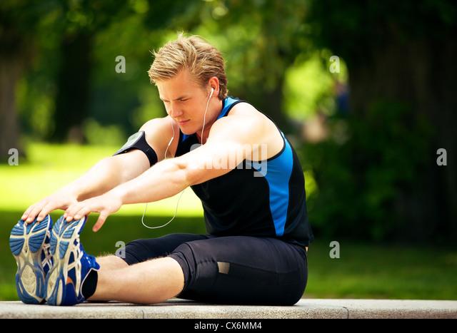 Attraktive Athlet seine stretching-Übung zu tun Stockbild