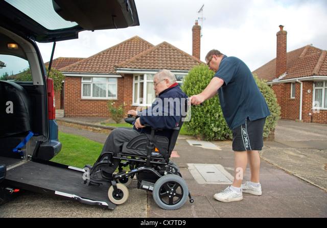 Männliche Pflegekraft Sohn schob einen behinderten älteren Mann im Rollstuhl auf eine eingebaute Rampe Stockbild
