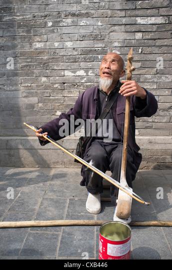 Blinder Mann als Straßenmusikant auf Straße im alten Bezirk von Peking beliebt bei Touristen am Houhai Stockbild