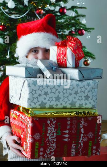 Boy holding Stack von Weihnachten präsentiert Stockbild